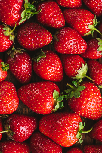 Fresh strawberries as a background. Food background fresh organic strawberries, vertical orientation