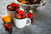Fresh strawberries in enameled cups and cherry with apricots in a metal colander
