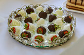 Fresh strawberries dipped in dark and white chocolate on plate.