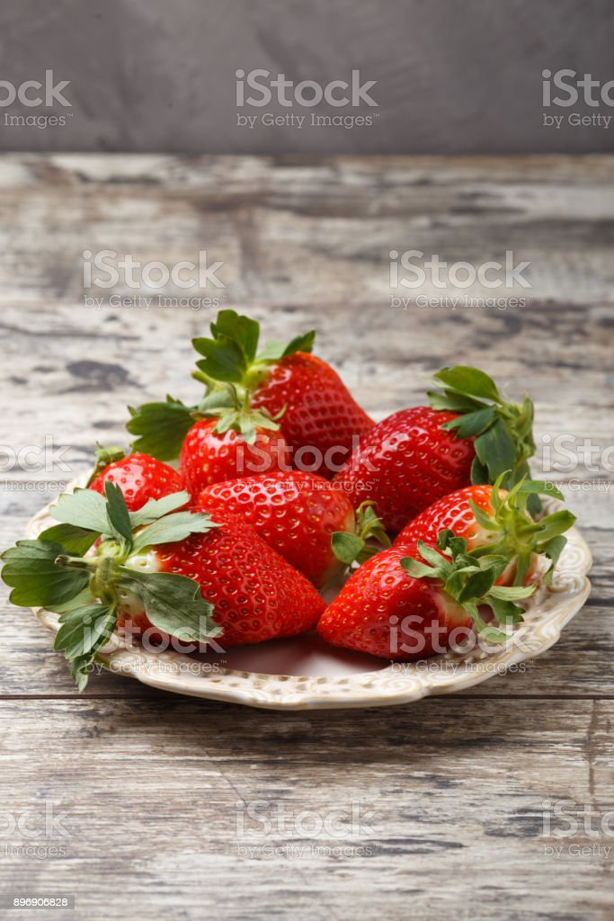 fresh strawberries in a plate on wooden background stock photo