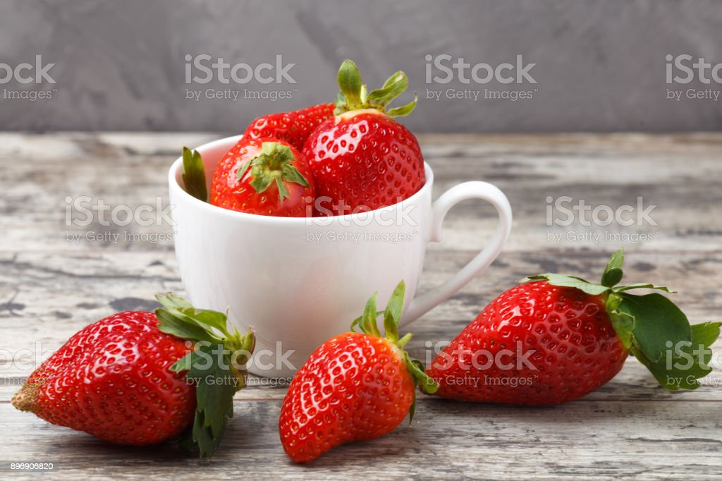fresh strawberries in a white cup on wooden background stock photo