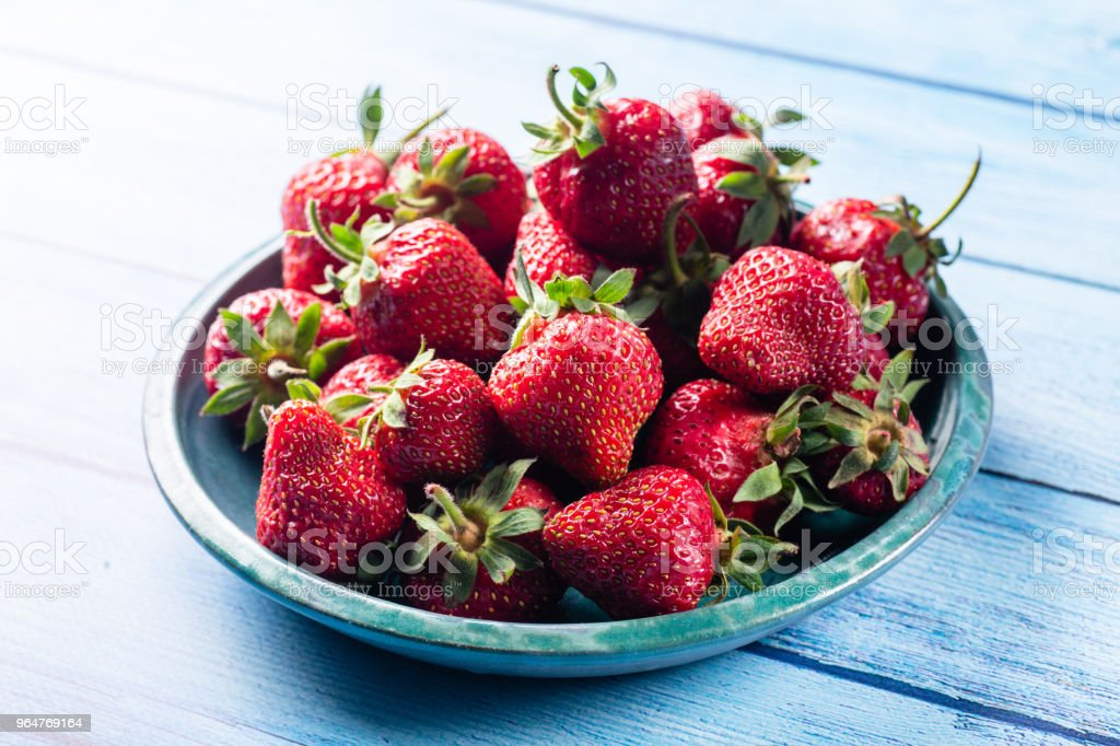 Fresh strawberries in green plate on blue wooden table royalty-free stock photo