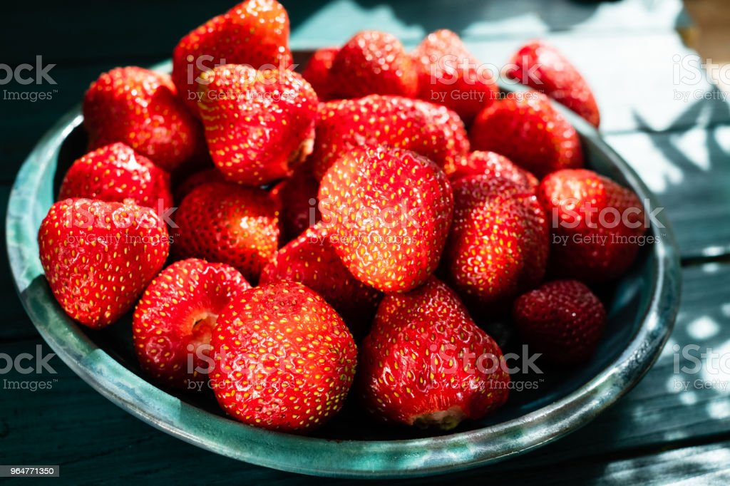Fresh strawberries in green plate on green wooden table royalty-free stock photo
