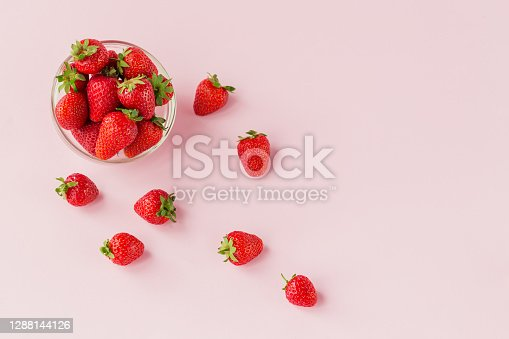 Fresh strawberries in transparent glass bowl flat lay. Healthy food on light pink table mock up. Delicious, sweet, juicy and ripe berry background with copy space for text