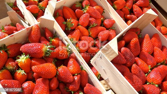 istock Fresh strawberries in wooden boxes at the farmers market, ready for sale 1081672032