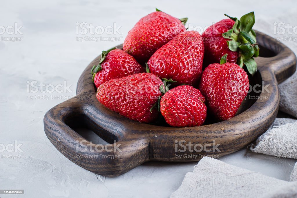 Fresh strawberries on wooden plate on white table background. Summer Berries. Copy space, top view - Royalty-free Basket Stock Photo