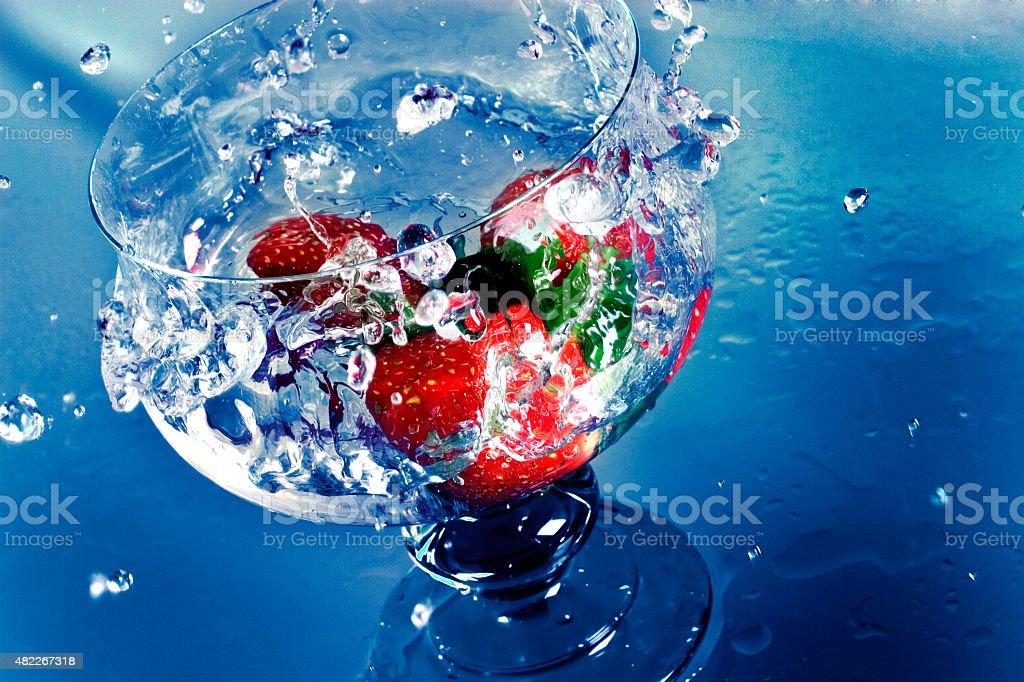 Morangos frescos respinga em um copo de água - foto de acervo