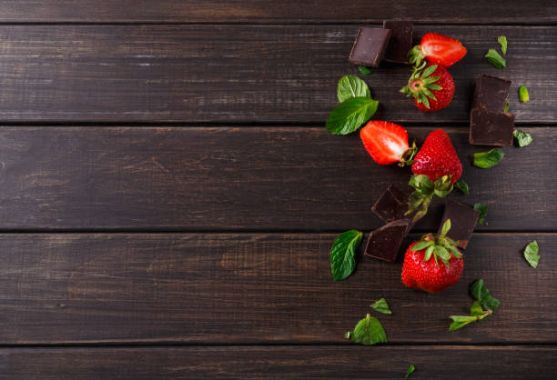 frische erdbeeren mit schokolade auf rustikalen tisch - fondue zutaten stock-fotos und bilder