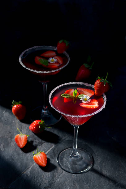 Fresh strawberry cocktail in a martini glass on dark stone background, decorated with fresh fruits, mint and a small flower. Copy space on top. stock photo