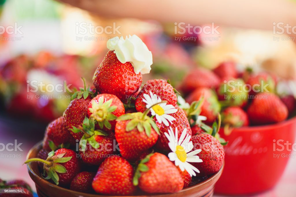 A fresh strawberry in a bowl on a table in a summer garden is adorned with chamomile flowers with a low key stage. Healthy eating and freshness - Royalty-free Abundance Stock Photo