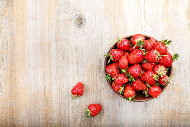 Fresh strawberry in a clay plate  on wooden table stock photo