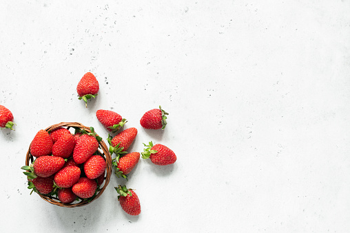 Fresh strawberry in bowl on bright gray concrete background