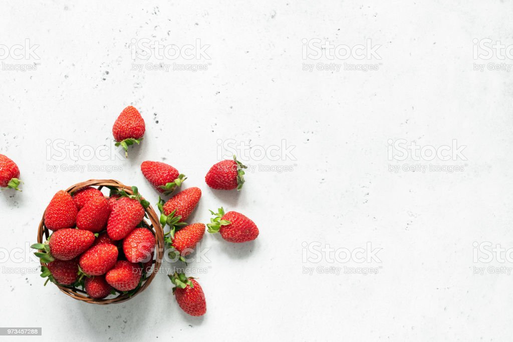 Fresh strawberry in bowl on bright gray concrete background stock photo