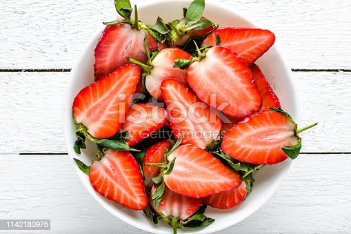 640978994 istock photo Fresh strawberry. Ripe berry slices on plate, top view. 1142180975