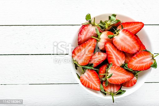 640978994 istock photo Fresh strawberry salad, top view in a bowl on wooden background, vegetarian food concept 1142180947