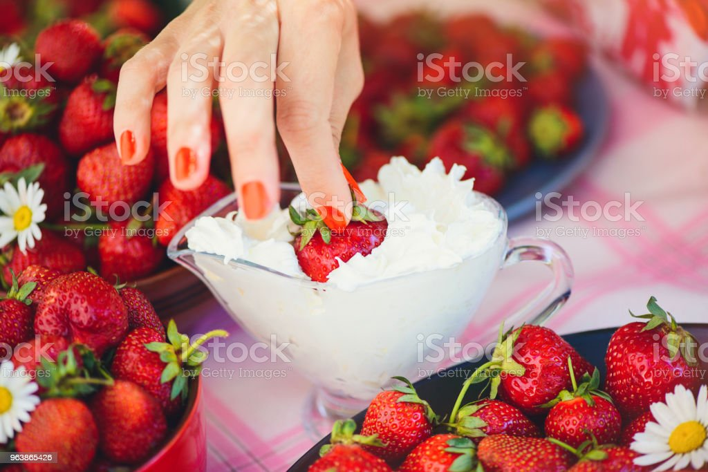 A fresh strawberry with cream in a bowl on a table in a summer garden is decorated with chamomile flowers the hand takes with a low key stage. Healthy eating and freshness - Royalty-free Berry Stock Photo