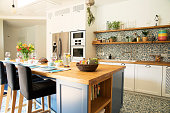 istock Fresh summer breakfast in Mediterranean style kitchen. Bright and sunny space with a lot of herbs and plants. Modern kitchen with open space. 1072989086