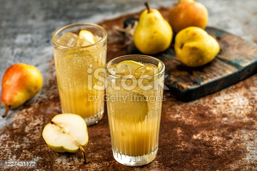 Fresh summer drink with ice and pear fruits on rustic background
