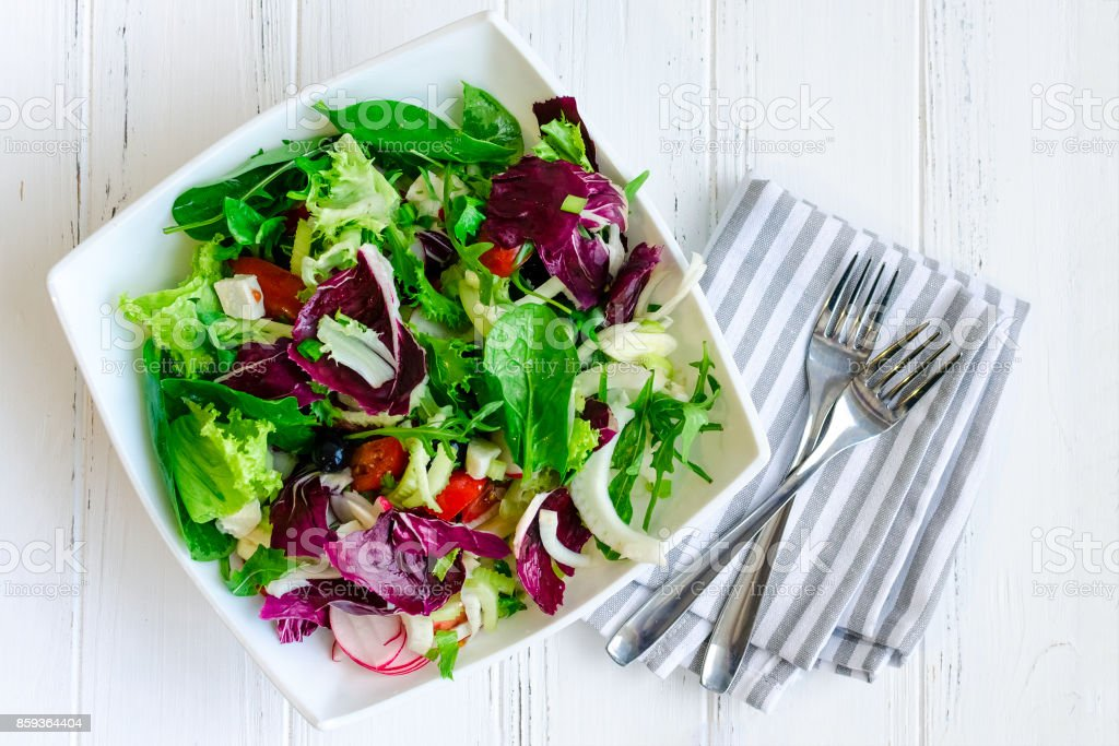 Fresh summer green salad mix on a wooden table stock photo
