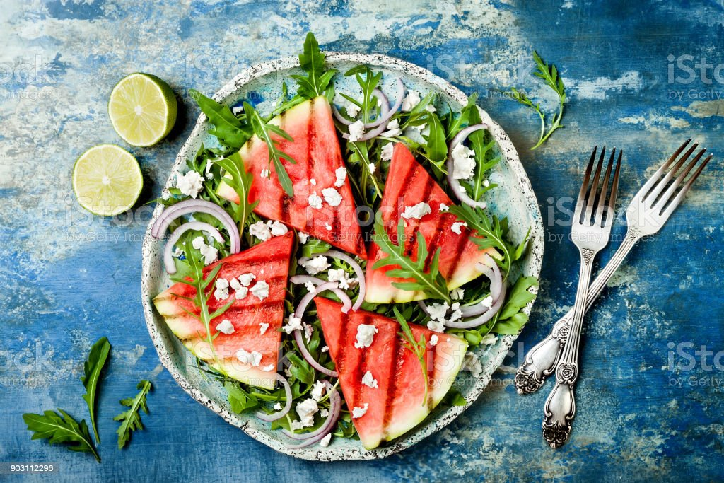 Fresh summer grilled watermelon salad with feta cheese, arugula, onions on blue background stock photo
