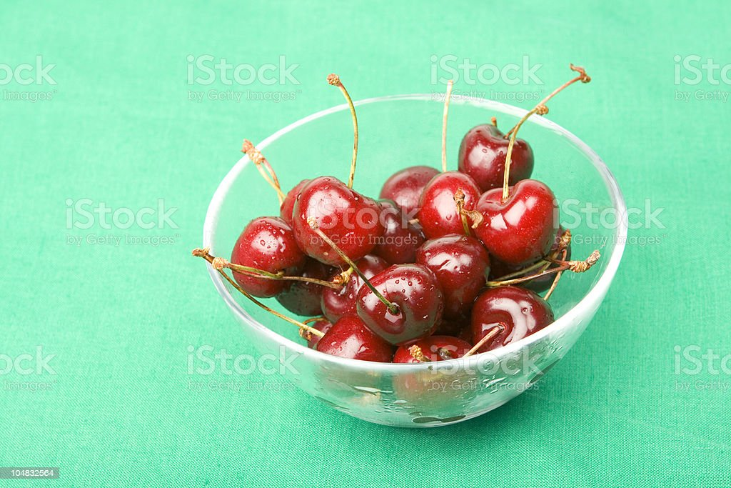 Fresh sweet cherries in glass bowl on green linen background stock photo