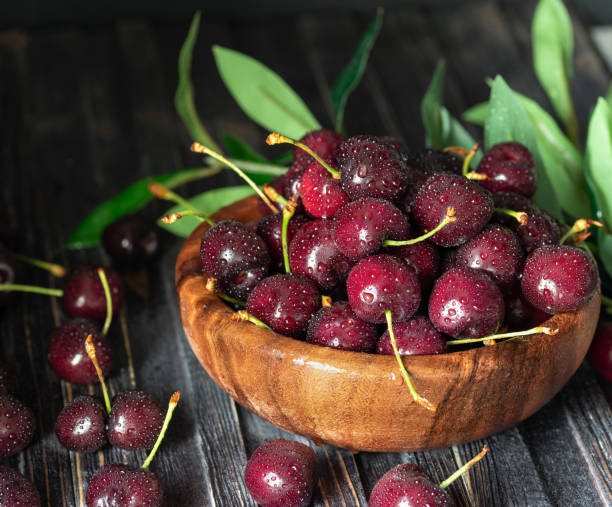 新鮮的甜櫻桃在板材在黑暗的木質背景與拷貝空間。夏天和收穫概念。櫻桃宏。素食, 素食, 生食。 - 車厘子 個照片及圖片檔