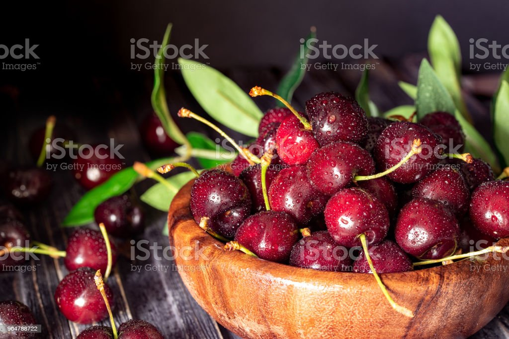 Fresh sweet cherries in plate on dark wooden background with copy space. Summer and harvest concept. Cherry macro. Vegan, vegetarian, raw food. royalty-free stock photo