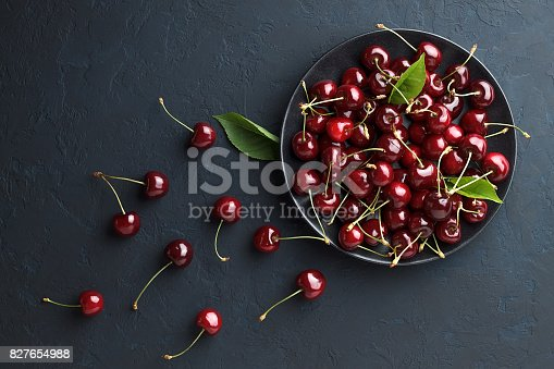 Fresh sweet cherry in black plate on dark blue stone background. Summer delicious berry. Top view with copy space.