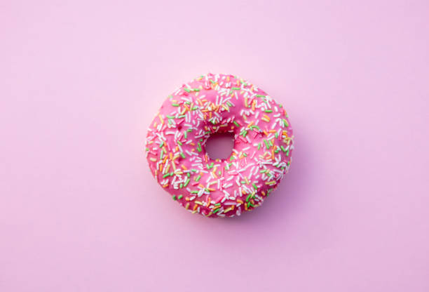 fresh sweet donut on pink background - bombolone foto e immagini stock