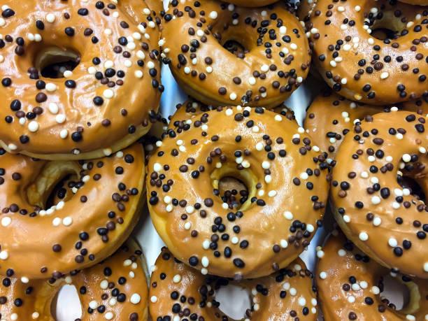 frische süße krapfen in schokoladenglasur mit farbigen süßwaren pulver - hausgemachte gebackene donuts stock-fotos und bilder