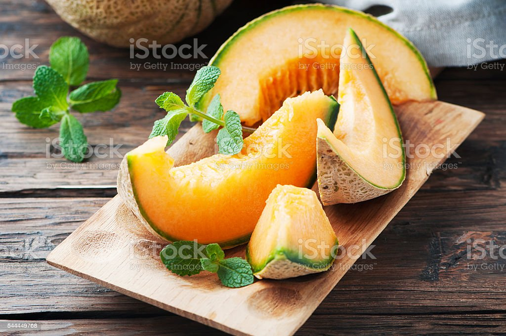 Fresh sweet orange melon and green mint stock photo