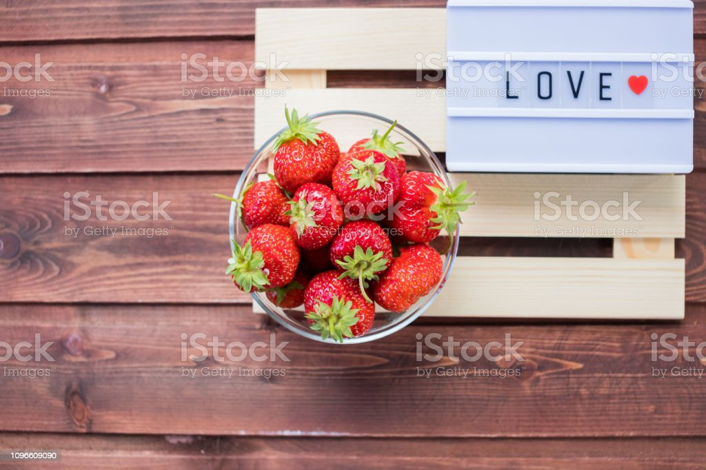 Fresh sweet strawberry on wooden table. Light box with message Love....