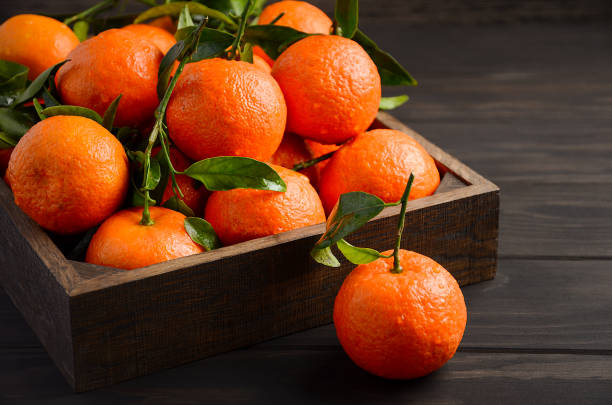 Fresh tangerine clementines with leaves on dark wooden background Fresh tangerine clementines with leaves on dark wooden background, selective focus, horizontal with copy space. tangerine stock pictures, royalty-free photos & images