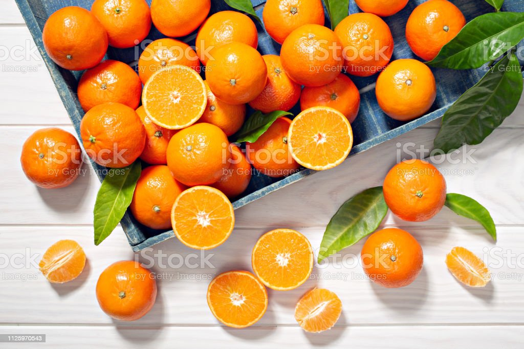 Fresh tangerine fruits with leaves on wooden table stock photo