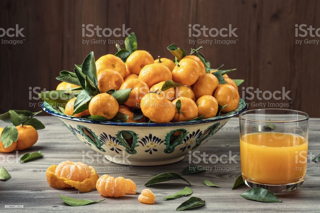 Fresh Tangerines (Mandarins) In Ceramic Dish With Green Leaves And Glass Of Juice On Textured Gray Wooden Table And Dark Background. Natural Day Light. Healthy Food Concept. stock photo