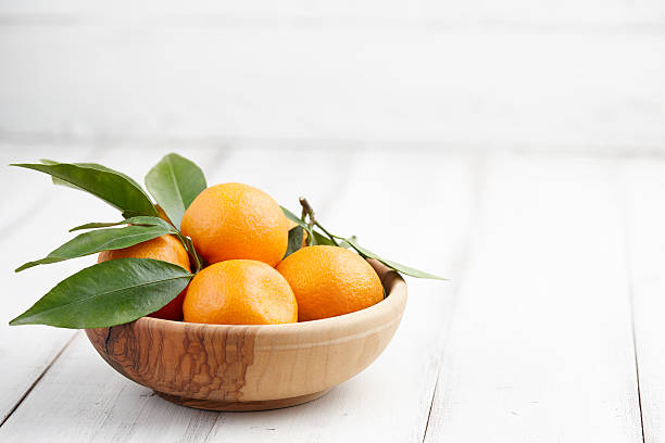 frische mandarinen mit blätter - obstkorb stock-fotos und bilder