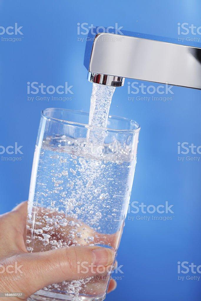 Füllen ein Glas Mineralwasser. Blau Hintergrund. – Foto