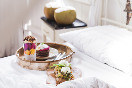 Fresh tasty breakfast in bed on wooden tray. Yogurt with fruits and chia, honey pancakes, two toasts with avocado and poached eggs and two young coconut. White vintage interior
