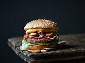 fresh tasty burger on old dark wooden table
