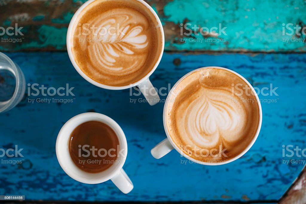 fresh tasty coffee cups two fresh tasty cappuccino coffee cups with latte art on it and one espresso cup on the coffee table 2015 Stock Photo