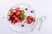 Fresh tasty mix fruit salad in the glass bowl on white table background. Healthy vitamin  breakfast Top view