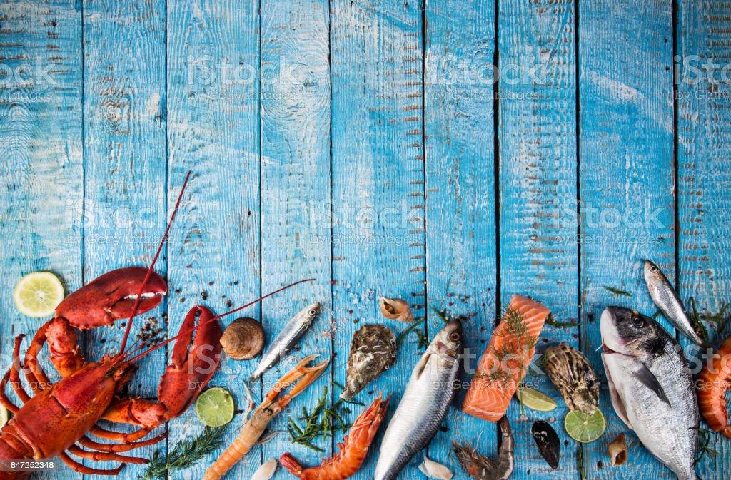 Sabrosos pescados y mariscos frescos servidos en mesa de madera vieja - foto de stock