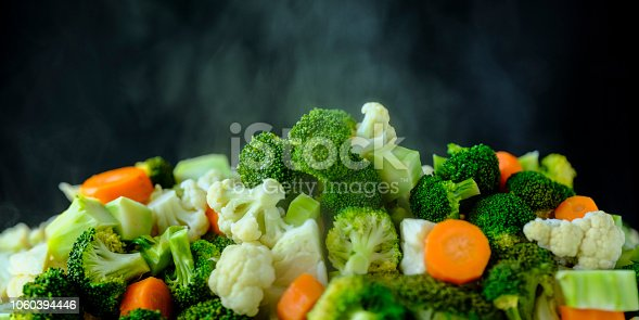 Fresh tender vibrant green steaming vegetables against a black background. Vegetables include broccoli, cauliflower, cabbage and carrots. Shallow depth of field.