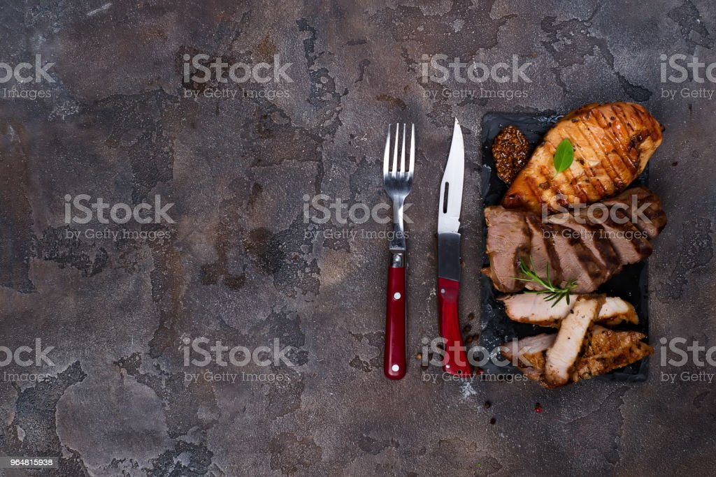 Fresh three types of grilled steak (chicken, pork, beef) on slate plate with herbs royalty-free stock photo