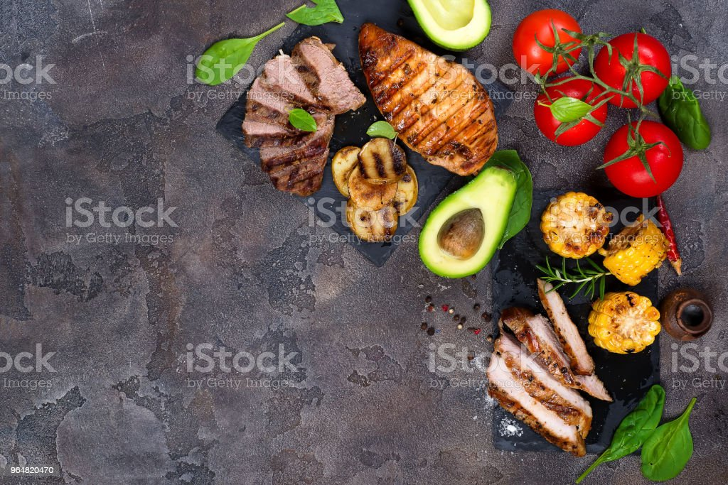 Fresh three types of grilled steak (chicken, pork, beef) on slate plate with herbs, tomato, avocado and grilled potatoes royalty-free stock photo