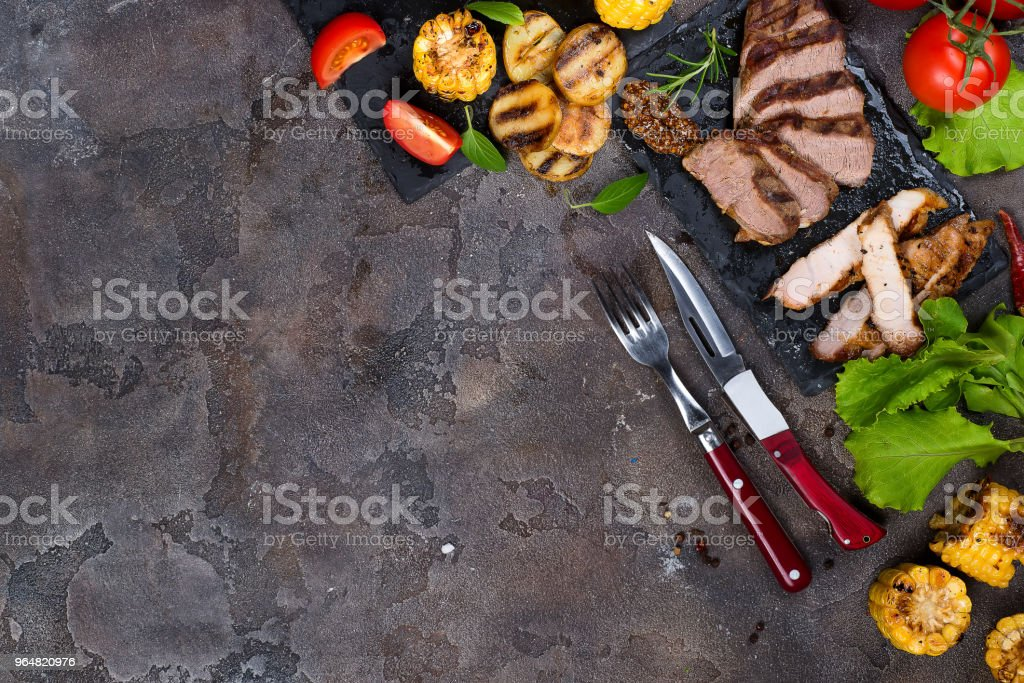 Fresh three types of grilled steak ( pork, beef) on slate plate with herbs, tomato and grilled potatoes royalty-free stock photo