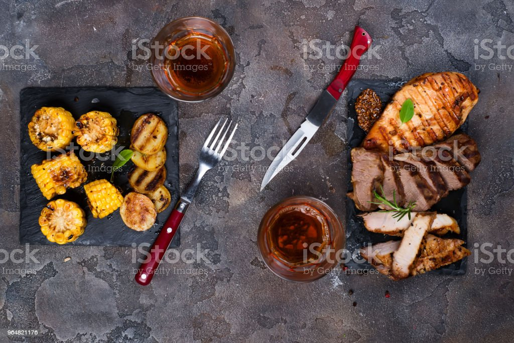 Fresh three types of grilled steak (chicken, pork, beef) on slate plate with herbs, tomato, juice, corn and grilled potatoes royalty-free stock photo