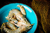 istock Fresh tiger prawns on a blue plate and dark background with fishing net 1297013679