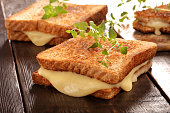 Fresh toast with cheese and herbs on wooden background\