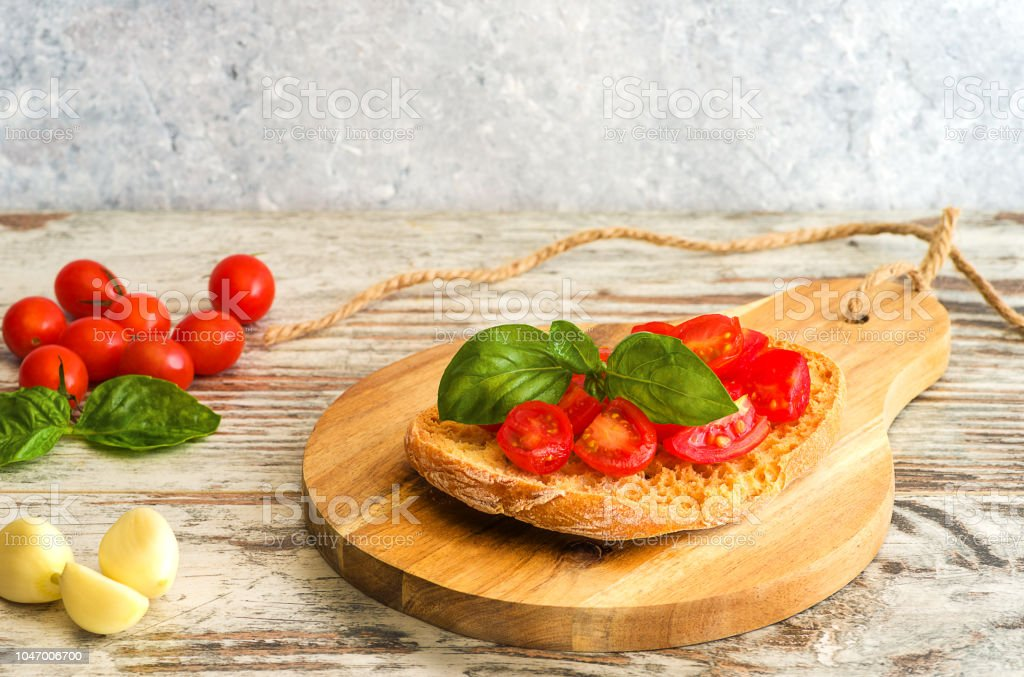 Fresh tomato bruschetta on wooden background, with basil and garlic - foto stock